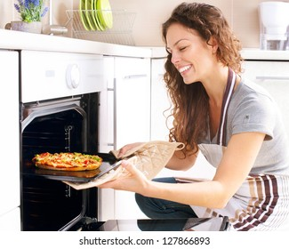 Happy Young Woman Cooking Pizza at Home. Oven