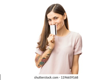 Happy young woman covering mouth with credit card over white background