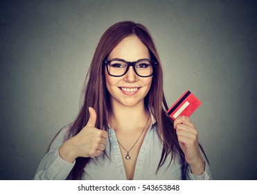 happy young woman with credit card giving thumbs up hand gesture