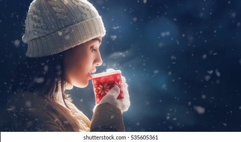 Happy young woman with a cup of hot tea on snowy winter walk in nature. Concept of frost winter season.