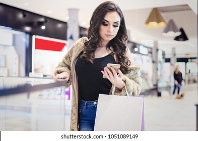 Happy young woman with curl hair and makeup holding bags with purchases, smiling while looking at phone in shopping center. Received good news, reading message, texting, dialing number