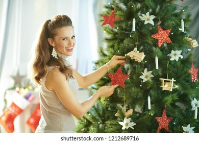 happy young woman decorating the Christmas tree