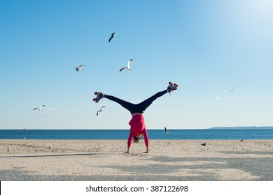 Happy young woman doing cartwheel on the beach wearing rollerskates. Portrait of woman on the beach doing a handstand with sea and seagulls in background.