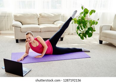 Happy young woman doing working out exercise on floor at home, online training on laptop computer, copy space. Yoga, pilates exercising. Sport, healthy lifestyle concept