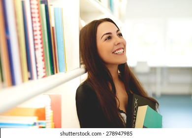 Happy young woman dreaming of her studies and subsequent opportunities in life standing clasping a book to her chest alongside a full bookcase looking up with a happy smile