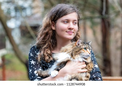 Happy young woman in dress holding maine coon cat outside, outdoors during summer in park