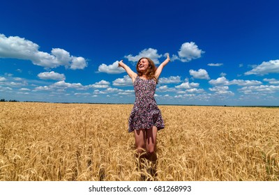 Happy young woman in dress jumping in golden wheat field with blue sky background, free space. Liberty, peace of mind wellness concept. Girl in spikes of ripe wheat field with hands up under blue sky