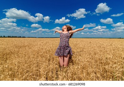 Happy young woman in dress jumping in golden wheat field with cloudy blue sky background, free space. Liberty, peace of mind concept. Girl in spikes of ripe wheat field with hands up under blue sky