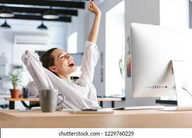 Happy young woman dressed in shirt sitting at her workplace at the office, resting, stretching her hands