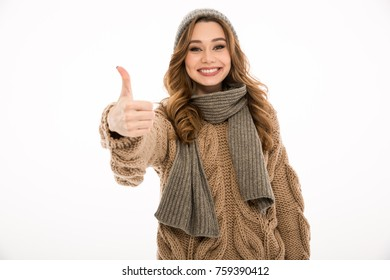Happy young woman dressed in warm sweater and scarf standing isolated over white wall background. Looking camera showing thumbs up.