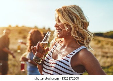 Happy young woman is drinking the beer and laughing in the sunset outdoor.
