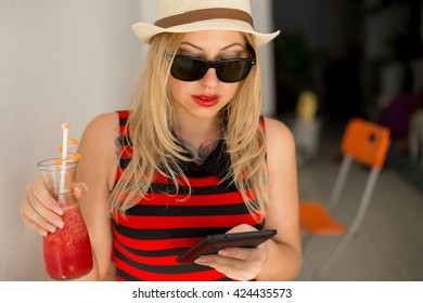 Happy young woman drinking coffee and using tablet computer. Woman  reading electronic book on her digital tablet,  browsing website pages on touch pad while breakfast in coffee shop