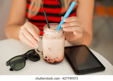 Happy young woman drinking coffee and using tablet computer. Woman  reading electronic book,browsing website pages on touch pad while breakfast in coffee shop.Beautiful girl working in the Internet.