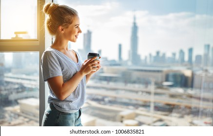 happy young woman drinks coffee in morning at big window