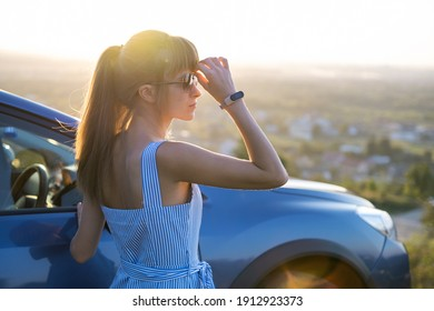 Happy young woman driver in blue dress enjoying warm summer evening standing beside her car. Travelling and vacation concept.