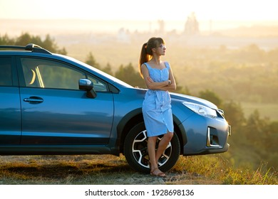 Happy young woman driver in blue dress leaning on her car enjoying warm summer day. Travelling and vacation concept.