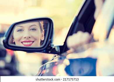 Happy young woman driver looking in car side view mirror, making sure line is free before making a turn. Human facial expressions, emotions. Safe trip, journey driving concept
