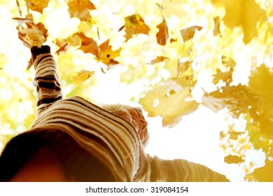 Happy young woman drop up autumn leaves