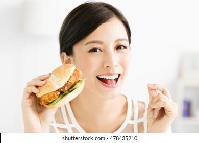 happy young  woman eating  big hamburger