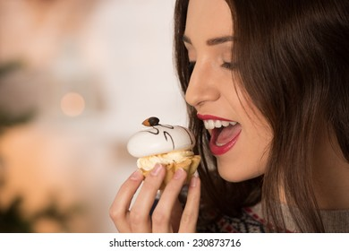 Happy young woman eating candy near christmas tree