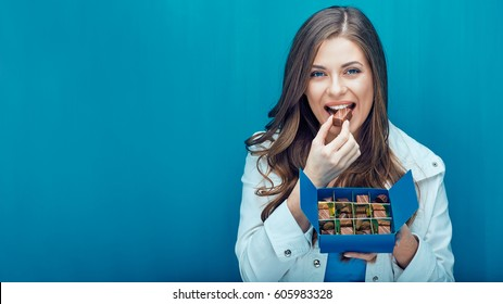 Happy young woman eating chocolate candies. Portrait against blue wall.