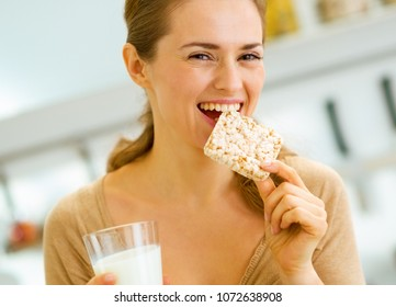Happy young woman eating crisp bread with milk in kitchen