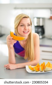 Happy young woman eating melon in kitchen