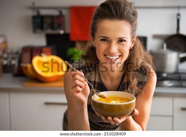 Joven feliz comiendo sopa de calabaza en la cocina