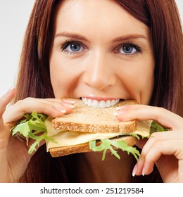 Happy young woman eating sandwich with cheese