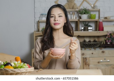 Happy young woman eating soup in kitchen