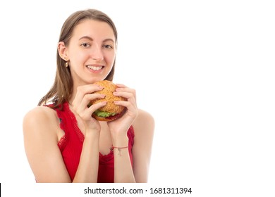 happy young woman eats cheeseburger on white background isolated looking at camera smiling