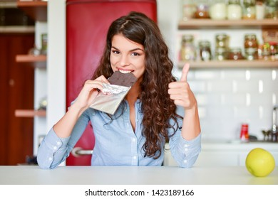 Happy young woman eats chocolate