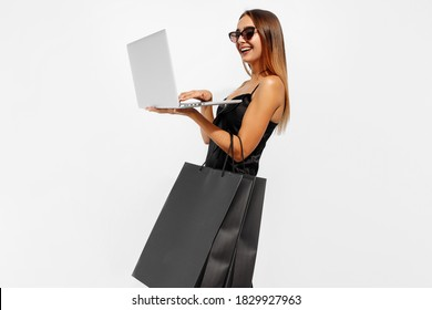 Happy young woman in elegant black dress and sunglasses, holds shopping bags and uses a laptop, on a white background, Online shopping, Black Friday