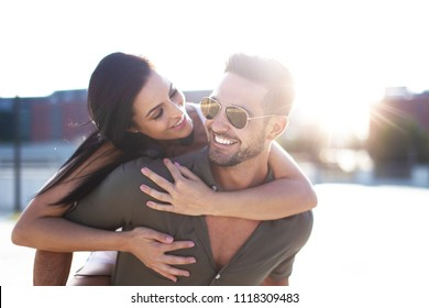 Happy young woman embracing stylish man from back outdoors in sunset