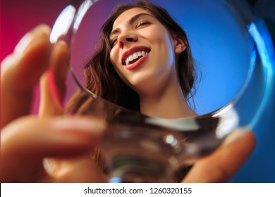 The happy young woman. Emotional female cute face. View from the glass