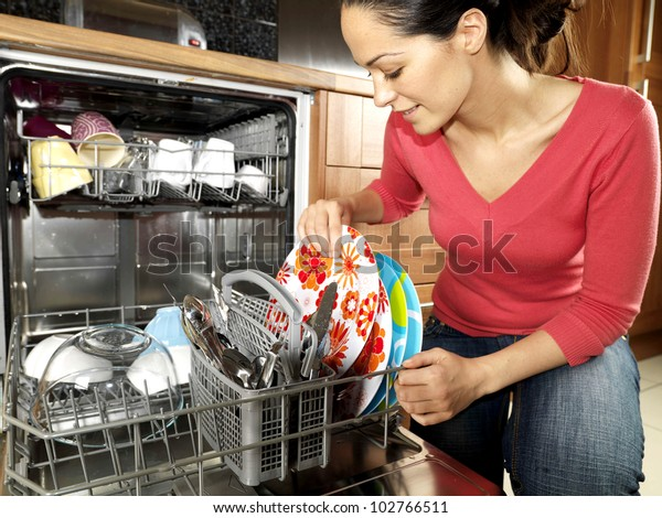 Happy Young Woman Emptying  Dishwasher After Washing Up Dishes And Cutlery Alone