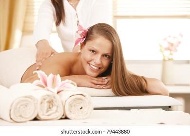 Happy young woman enjoying back massage, looking at camera, smiling.