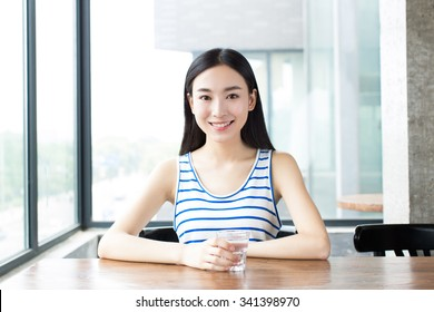 happy young woman enjoying drinking ginger tea with lemon