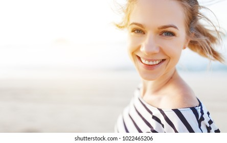 happy young woman enjoying freedom and laughs  on sea