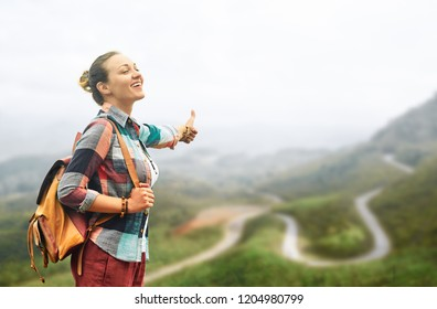 Happy young woman enjoying freedom with up hand on road.Summer vacation car road trip freedom concept.
