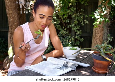 happy young woman enjoying healthy salad bowl reading magazine outdoors