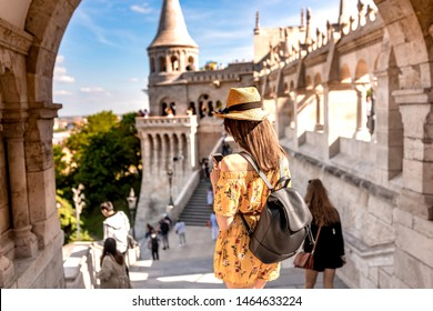A happy young woman enjoying her trip to the Castle of Budapest in Hungary while taking pictures and selfies.