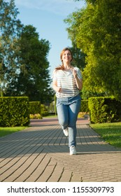 Happy young woman enjoying morning jogging in a summer park
