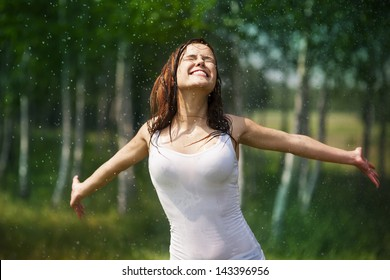 Happy young woman enjoying the rain in summer