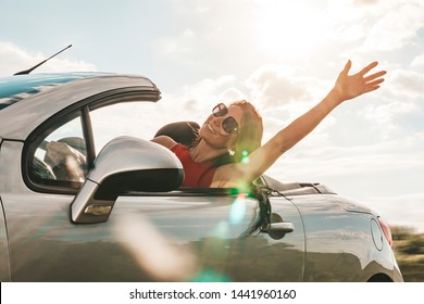 happy young woman enjoying a ride in a convertible car. hand greeting. The concept of road travel and adventure. riding with open roof flight effect.