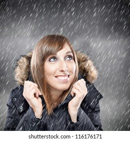 Happy young woman enjoying snow in winter