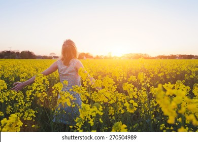 happy young woman enjoying summer in yellow field at sunset