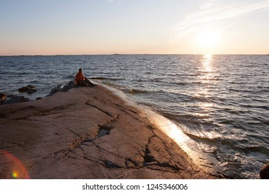 happy young woman, enjoying sunset at midsummer in the Aland Islands between Finland and Sweden