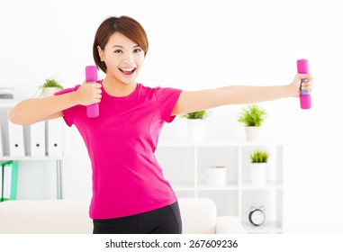 happy young woman exercising with dumbbells in living room