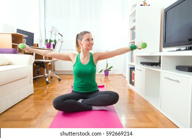 Happy young woman is exercising at home. She is sitting crossed-legged on the mat and doing exercise for her arms with a pair of green hand weights.